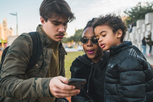 Portrait of lovely mixed race ethnic family having fun, relaxing and using mobile phone at the park outdoors.