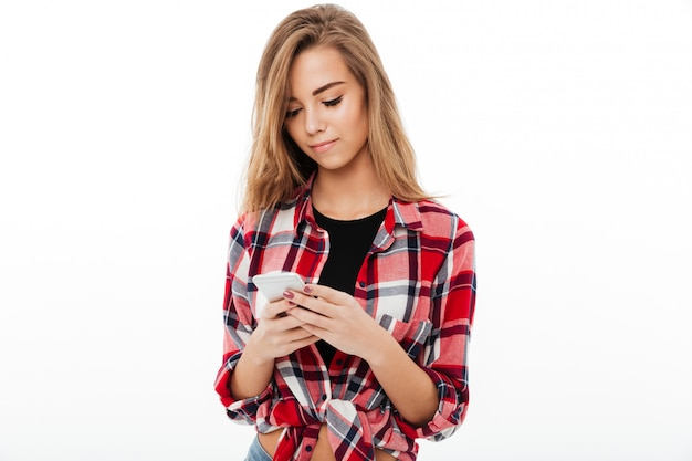 Portrait of a lovely pretty girl in plaid shirt texting