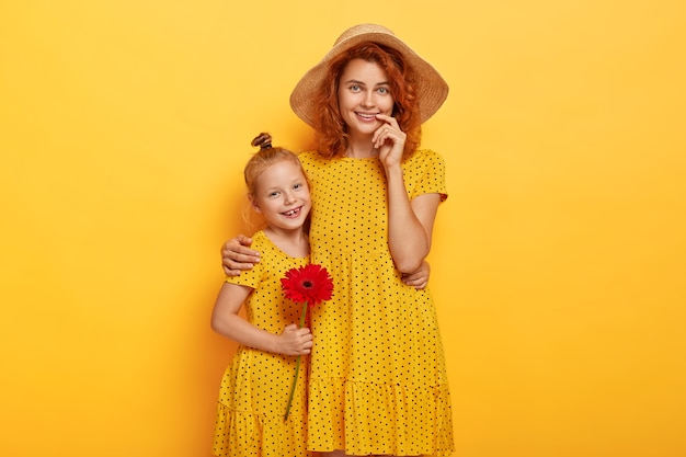 Portrait of lovely redhead mother and daughter posing in similar dresses