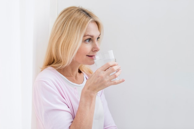 Portrait of lovely senior woman drinking water