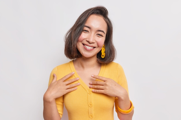 Il ritratto di una donna asiatica sincera e adorabile con i capelli scuri inclina la testa si sente felice si sente felice indossa un maglione giallo isolato su un muro bianco