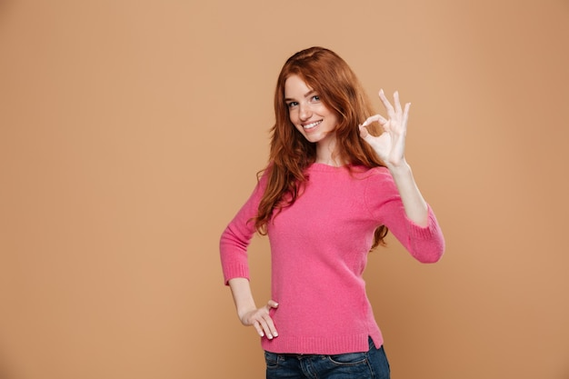 Portrait of a lovely smiling redhead girl making the ok gesture