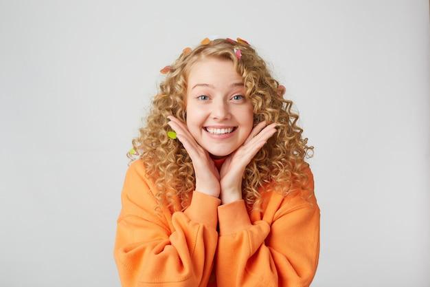 Ritratto di bella tenera bella bionda sembra eccitato, sorpreso, tiene i palmi vicino al viso, vestito con un maglione arancione oversize, isolato su un muro bianco