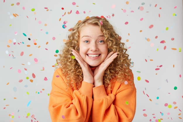 Portrait of lovely tender nice blonde looks excited, surprised, keeps palms near face, dressed in oversized sweater, stands under falling confetti