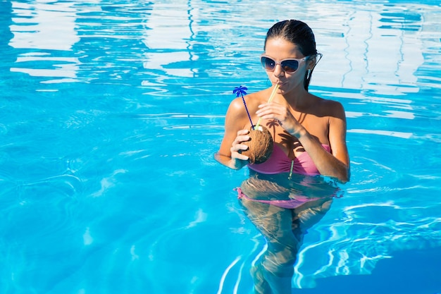 Portrait of a lovely woman drinking cocktail in swim pool outdoors