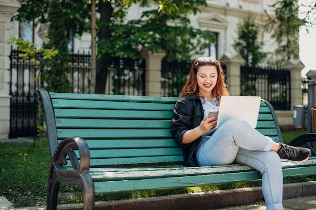 Portrait of a lovely woman sitting on beach with a laptop on her legs looking at the screen of a smartphone smiling outside.