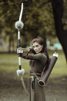 Portrait of lovely woman with arrows and bow, aiming at target