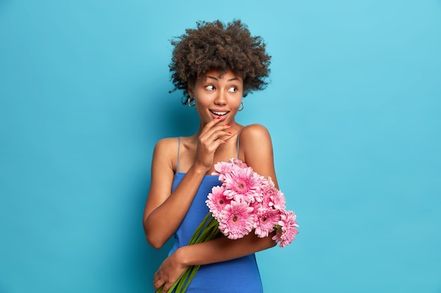 Portrait of lovely woman with curly hair wears dress dressed in festive clothes holds bouquet of gerbera flowers on first date looks gladfully aside isolated over blue wall