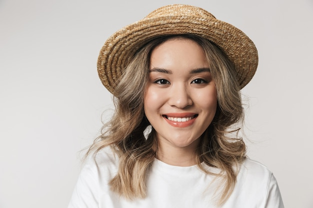 Portrait of a lovely young asian woman standing isolated over white wall, wearing summer hat, posing