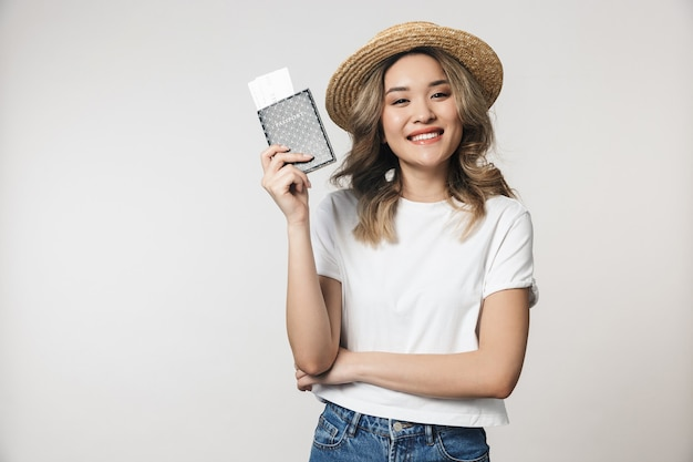 Portrait of a lovely young asian woman standing isolated over white wall, wearing summer hat, showing passport with flight tickets