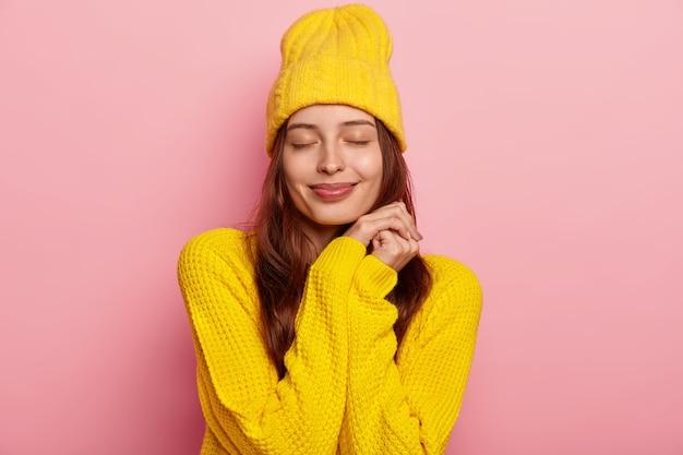 Ritratto di bella giovane donna europea tiene gli occhi chiusi, indossa un maglione lavorato a maglia giallo vivido e copricapo, isolato su sfondo rosa.