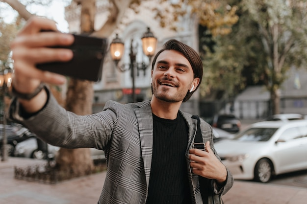 Portrait of lovely young gentleman in black t-shirt and plaid vintage blazer, making selfie against city landmark wall and smiling