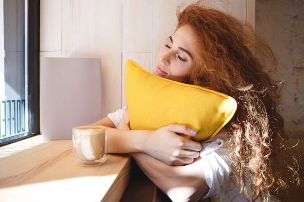 Portrait of a lovely young red hair woman hugging pillow