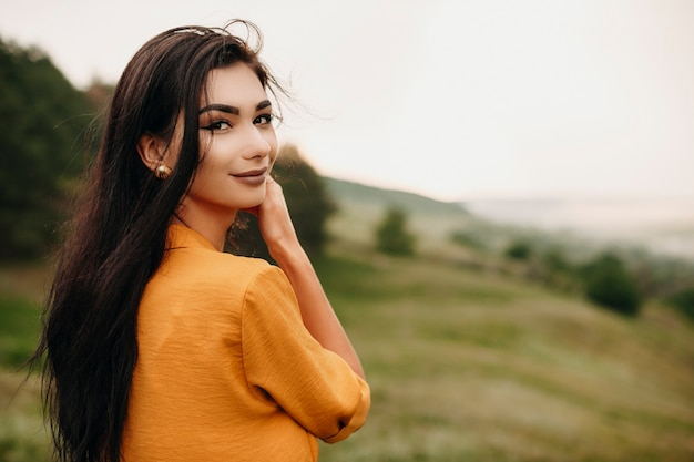 Portrait of a lovely young woman looking at camera smiling. charming young female with dark hair looking over shoulder at the photographer outdoor on a field.