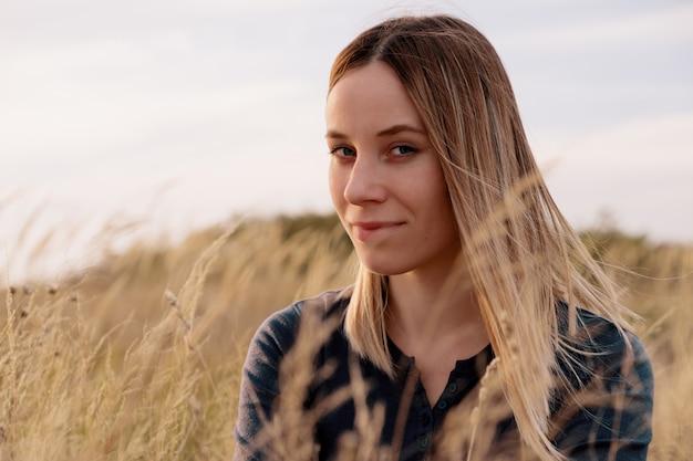 필드에서 편안한 세로 사랑스러운 젊은 여자 무료 사진