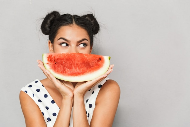 Portrait of a lovely young woman in summer dress isolated, holding watermelon slice