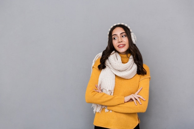 Portrait of a lovely young woman wearing sweater and scarf isolated over gray background, looking away