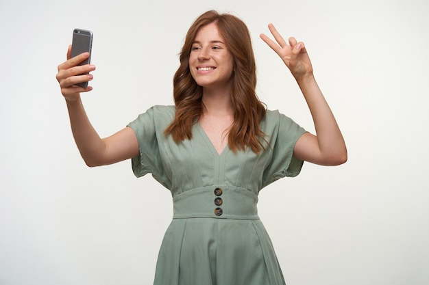 Portrait of lovely young woman with broad smile and romantic hairstyle standing, making selfie on her mobile phone, showing peace gesture