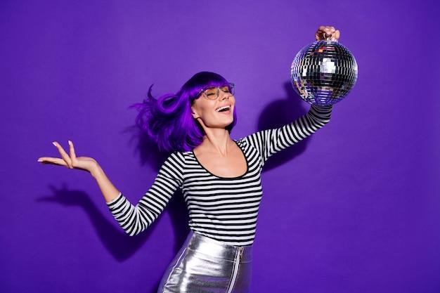 Portrait of lovely youth holding mirror ball close eyewear eyeglasses eyewear skirt isolated over violet purple background