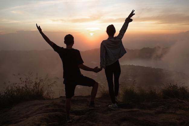 ポートレート。恋人たちは夜明けにバトゥール火山に寄り添います。バリ島インドネシア