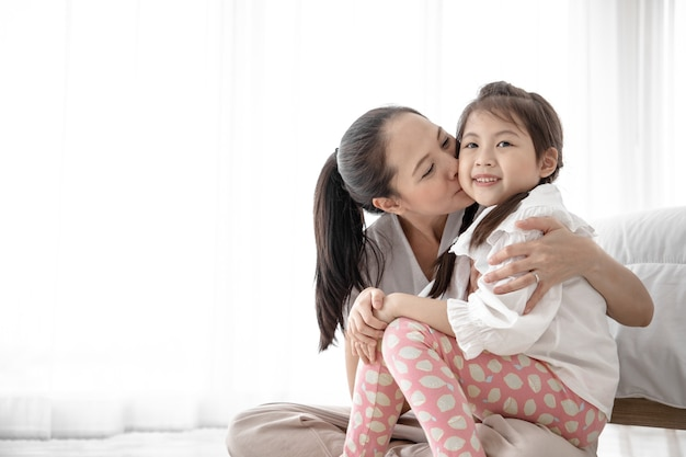 Portrait of lovey mother kiss her cute daughter on bed in the bedroom. they have happiness in freetime and relieve loneliness.