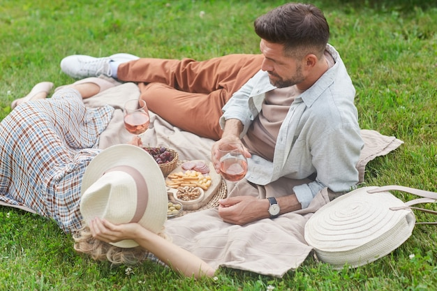 Portrait of loving adult couple enjoying picnic on green grass and drinking wine during romantic date outdoors