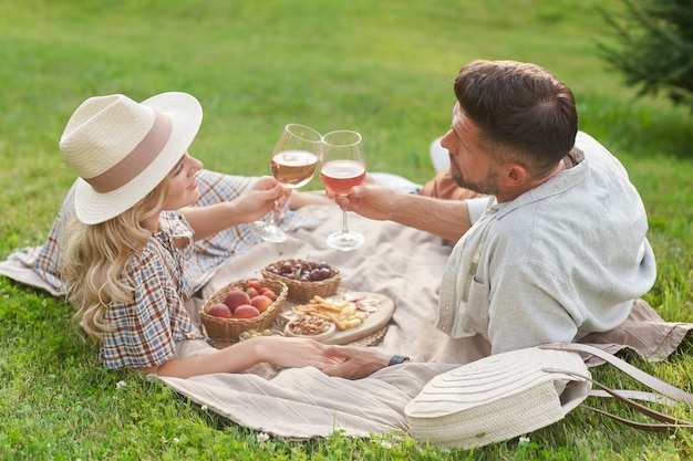 Portrait of loving adult couple enjoying picnic in sunlight and clinking wine glasses during romantic date outdoors