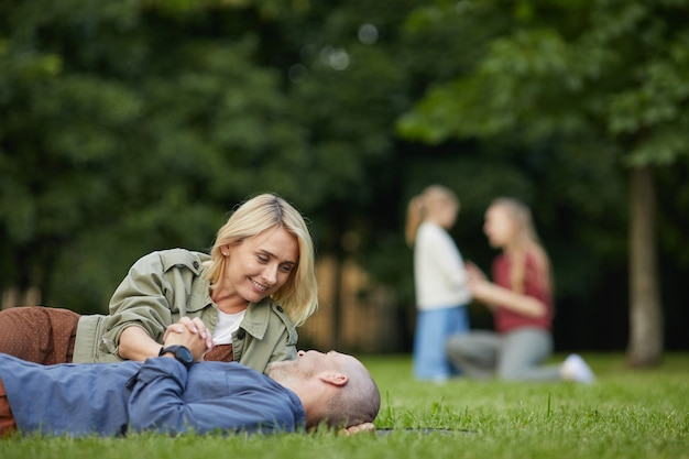 Portrait of loving adult couple laying on green grass in park and enjoying time together outdoors