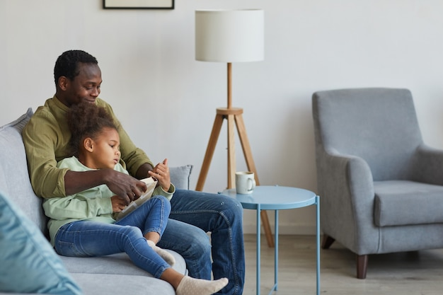 Portrait of loving african-american father and daughter sitting on couch together in cozy home interior, copy space