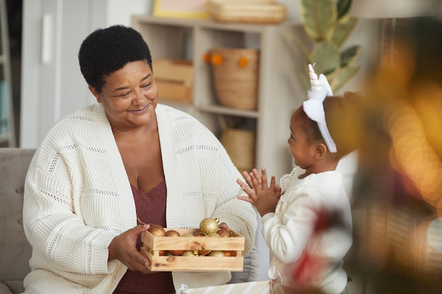 Portrait of loving african-american grandma decorating christmas tree with cute little girl while enjoying holiday season, copy space