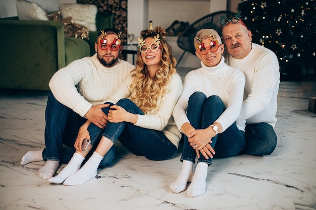 Portrait of loving cheerful family in sweaters and jeans wearing funny festive christmas glasses.