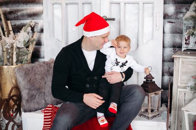 Portrait of loving dad with daughter on his shoulders decorating beautiful christmas tree with toys and decoration at home