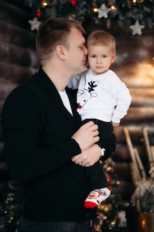 Portrait of loving dad with son on his shoulders decorating beautiful christmas tree with toys and decoration at home