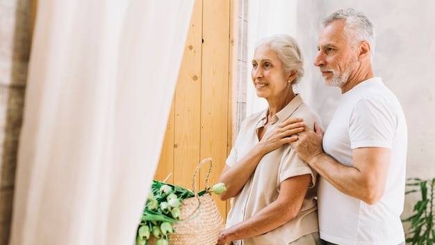 Portrait of loving happy senior couple looking away