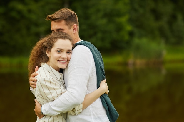 Portrait of loving young couple embracing standing by lake outdoors in summer