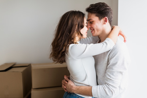 Portrait of loving young couple embracing standing in front of cardboard boxes