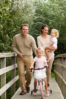 Portrait of loving young family of four on small bridge in the park