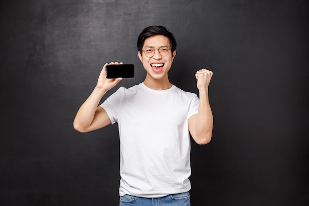 Portrait of lucky excited asian guy winning money on sport bet, fist pump and celebrating, showing his best score in mobile game on display, hold smartphone and triumphing,