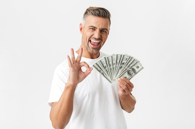 Portrait of lucky man 30s wearing casual t-shirt celebrating while holding bunch of money banknotes isolated on white