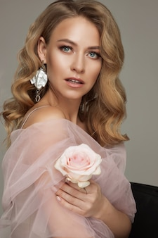 Portrait of luxury blonde woman with perfect makeup posing holding pink rose