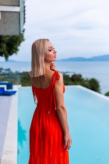 Portrait of luxury looking woman in red orange evening dress in rich hotel