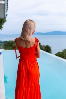 Portrait of luxury looking woman in red orange evening dress in rich hotel