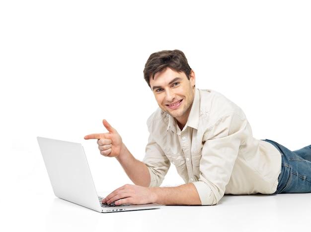 Ritratto di un uomo sdraiato con laptop e punti sullo schermo isolato su bianco.