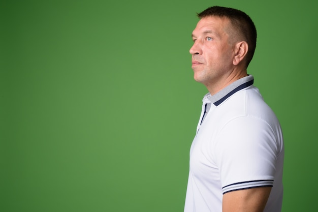 Portrait of macho mature man against chroma key with green wall