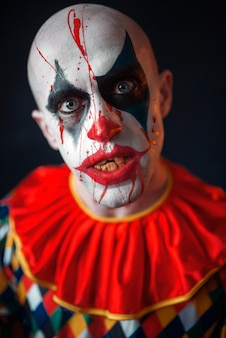 Portrait of mad bloody clown, face in blood. man with makeup in halloween costume, crazy maniac