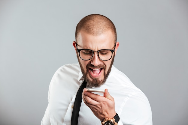 Portrait of a mad businessman yelling at mobile phone