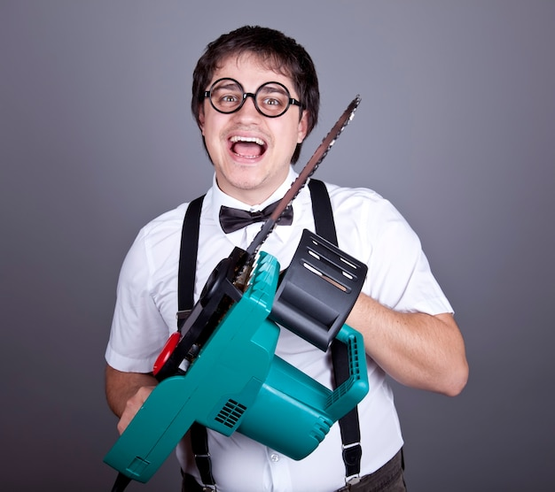 Portrait of mad fashion men in suspender with bow tie and glasses keeping portable saw.