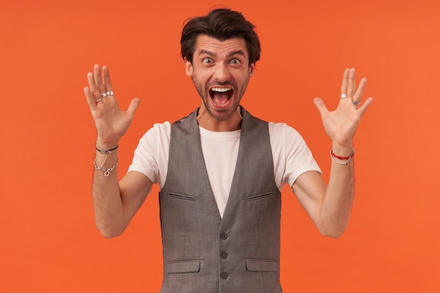 Portrait of mad furious young man with stubble and raised hands looks mad and shouting