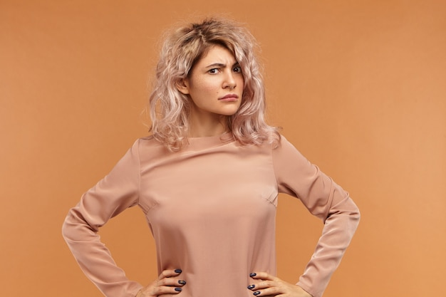 Portrait of mad young woman with voluminous hairstyle keeping hands on her waist,