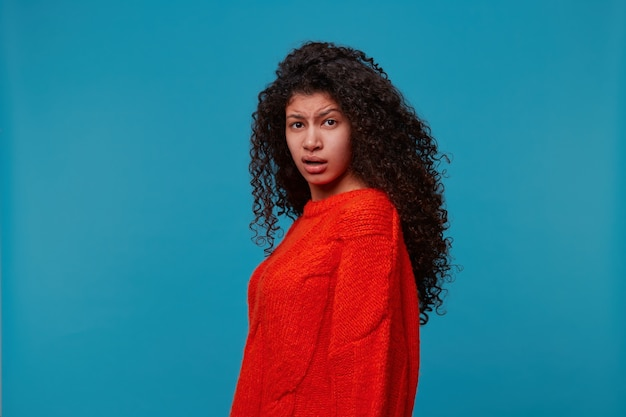Portrait of magnificent confused curly-haired woman in casual red sweater showing uncertainty misunderstanding